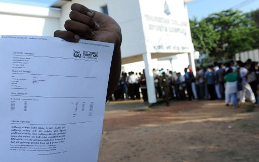 A Sri Lankan cricket fan holds up a receipt after buying tickets for the International Cricket Council Twenty20 World Cup that went on sale in Colombo on March 26, 2012. Hundreds of fans braved hot humid weather to stand in line outside the ticket booth in Colombo.
