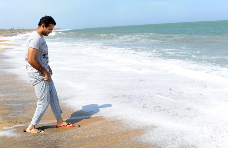 Indian cricketer Irfan Pathan walks along the beach in Hambantota on July 20, 2012.