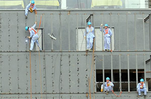 Chinese construction workers are seen working at The Mahinda Rajapaksa International Cricket Stadium in the southern district of Hambantota on December 8, 2010. AFP PHOTO/Lakruwan WANNIARACHCHI.