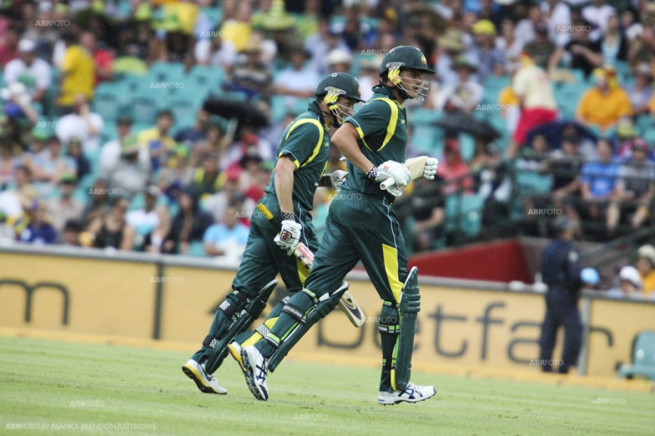 McKay and David Hussey run off the field as rain interrupts play