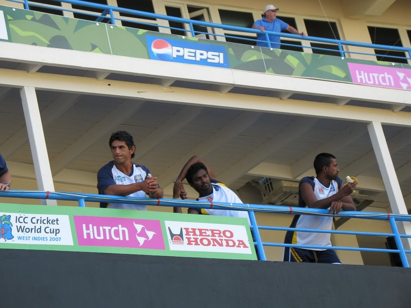 Murali stretching his shoulder, as Arnold relishes a banana