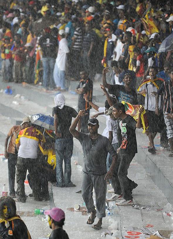 Sri Lankan cricket fans party in the rain.