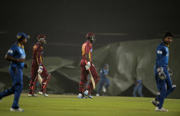 Players walk off as rain stops play