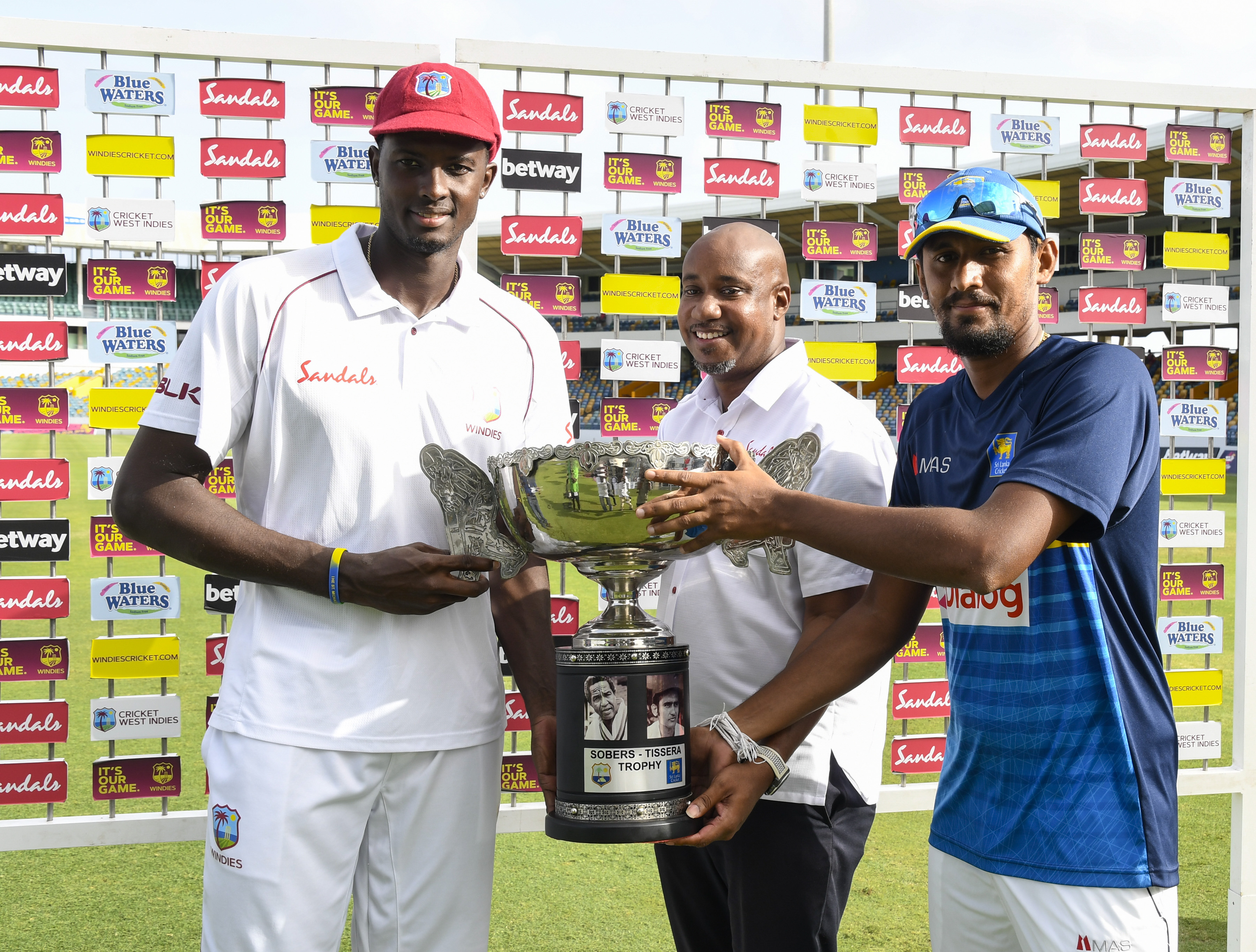 Jason Holder and Suranga Lakmal pose with the Sobers-Tissera Trophy